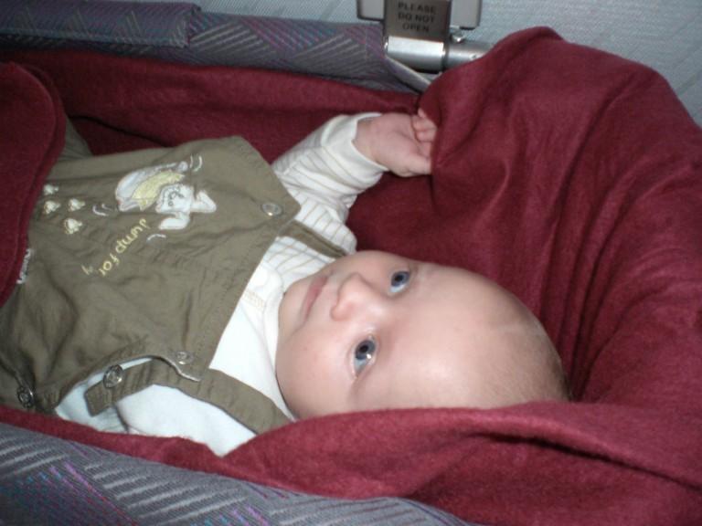 Baby liegt im Flugzeug im Baby Bett