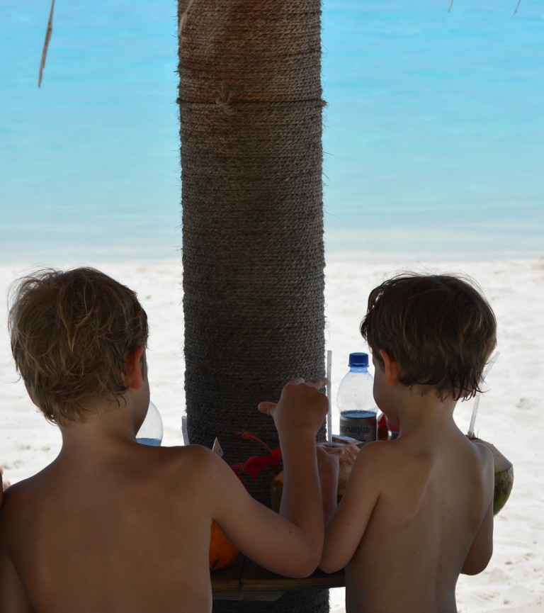 Kinder am Strand mit Kokosnuss